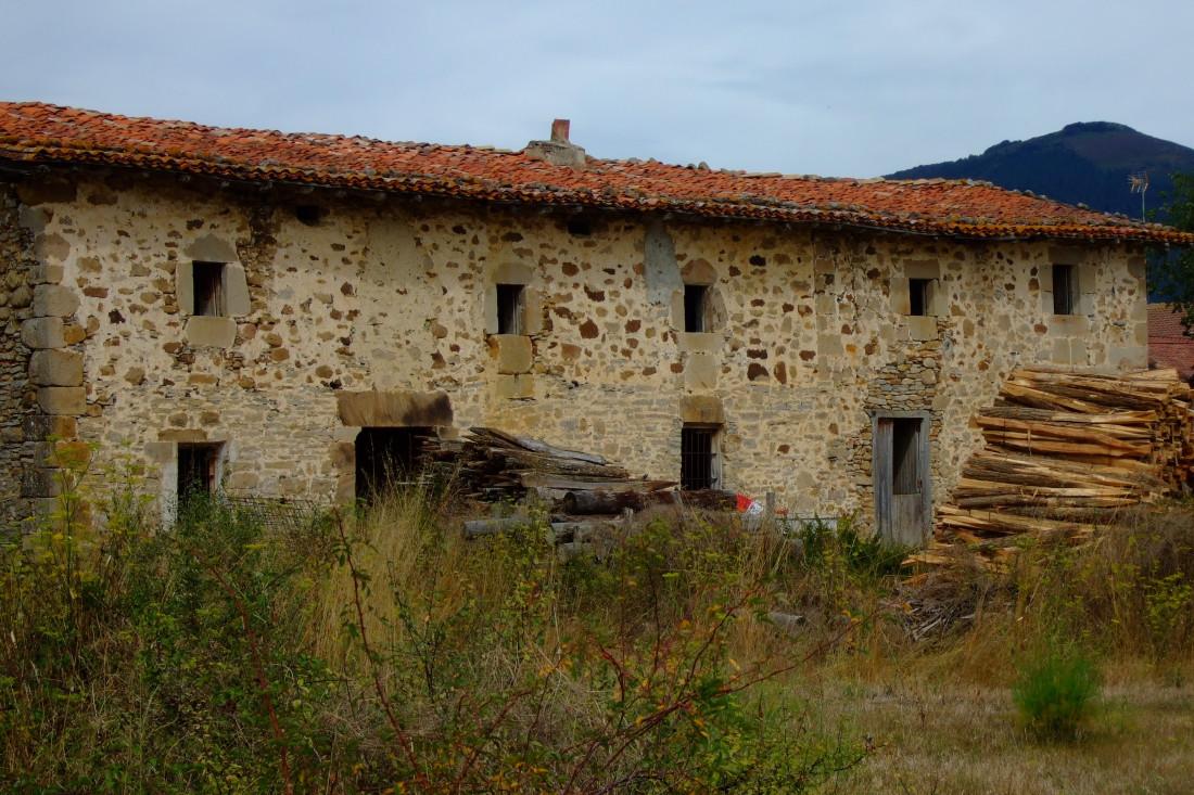 Pilas de leña junto a un viejo caserío. Narvaja.