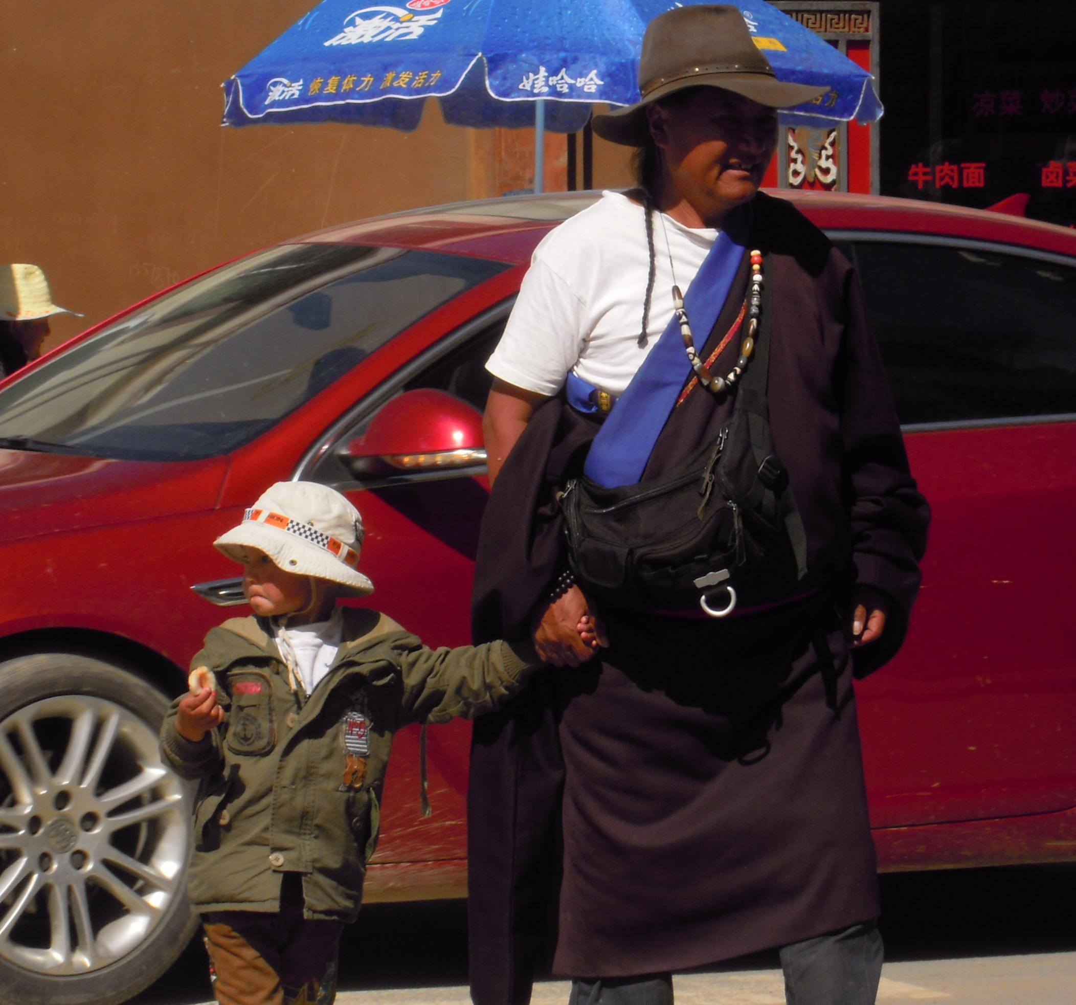 Pa and son crossing the street in Hongyuan.