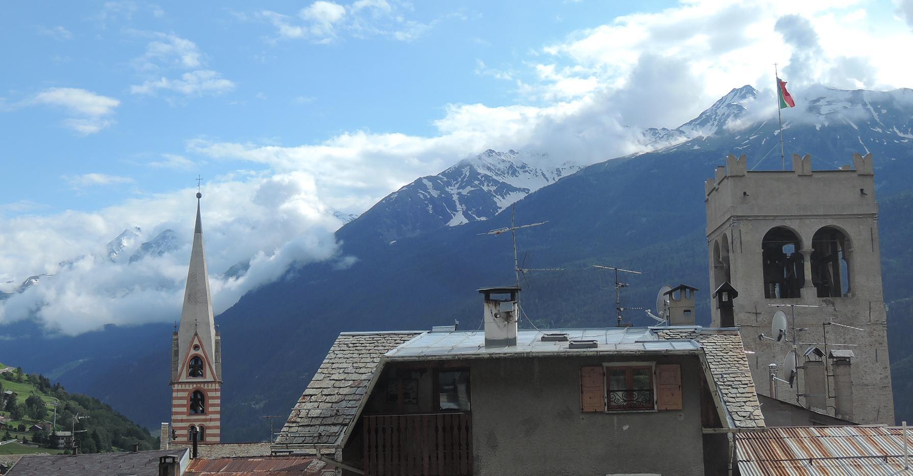 Torre campanario y tejados de Bormio junto a las cimas alpinas.