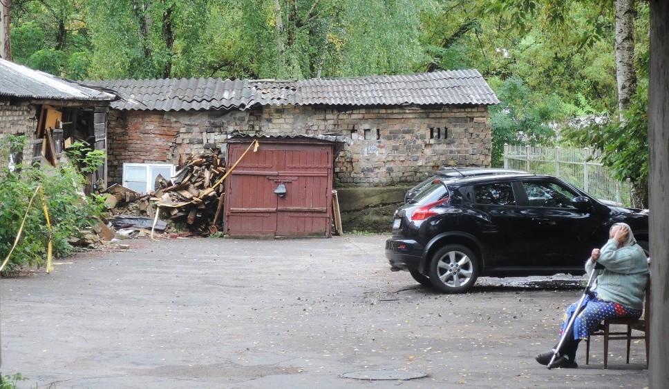 Una anciana a la entrada de un patio interior que alberga un aarboleda